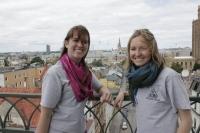 Kristīne Ģiga un Aina Budrēvica ar Rīgas skatu fonā Jēzus baznīcas tornī